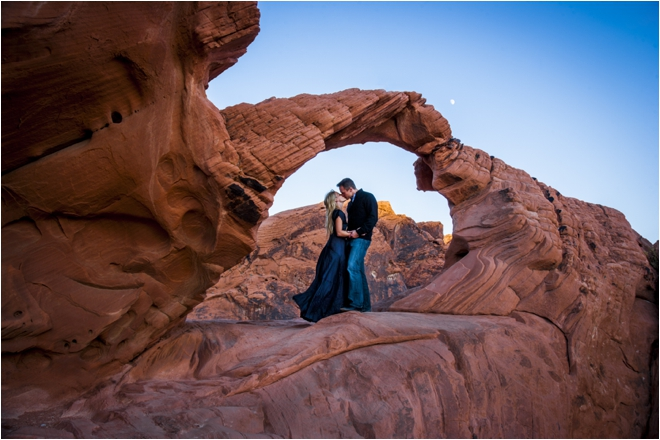 couple kissing in front of red rocks
