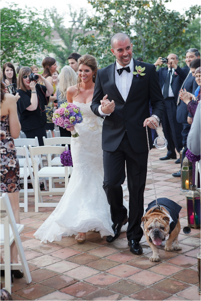 couple walking down aisle with dog