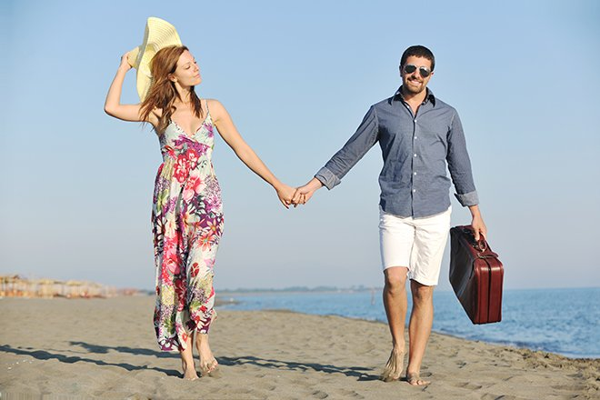 couple on beach with travel bag representing freedom and fun honeymoon concept