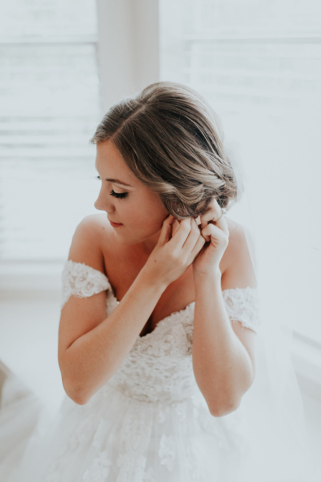 real wedding houston wedding the woodlands resort & conference center bride getting ready wedding day prep bridal jewelry white off the shoulder wedding dress braided updo