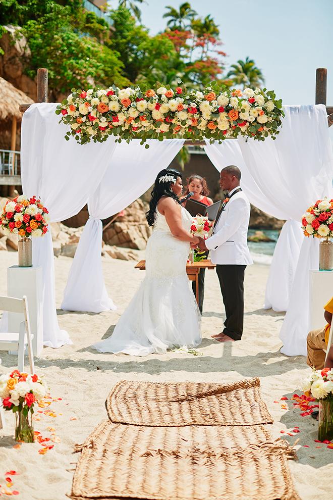 beach destination wedding, wedding ceremony, exchanging vows, floral wedding canopy, summer wedding, Mexico