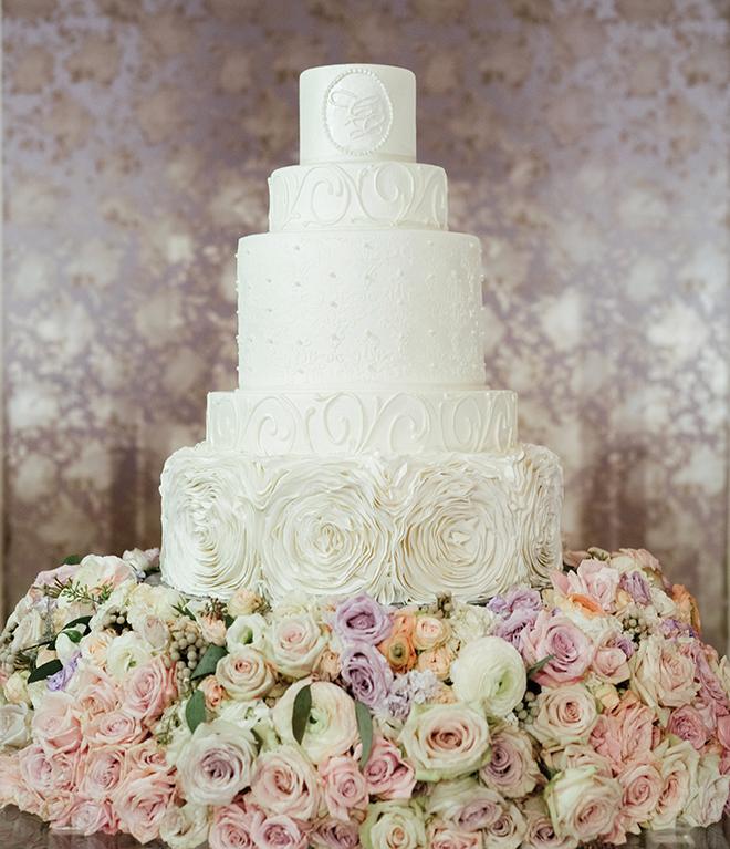 custom wedding cakes white multi-tiered wedding cake flower base detailing roses wedding cake inspiration monogrammed cake