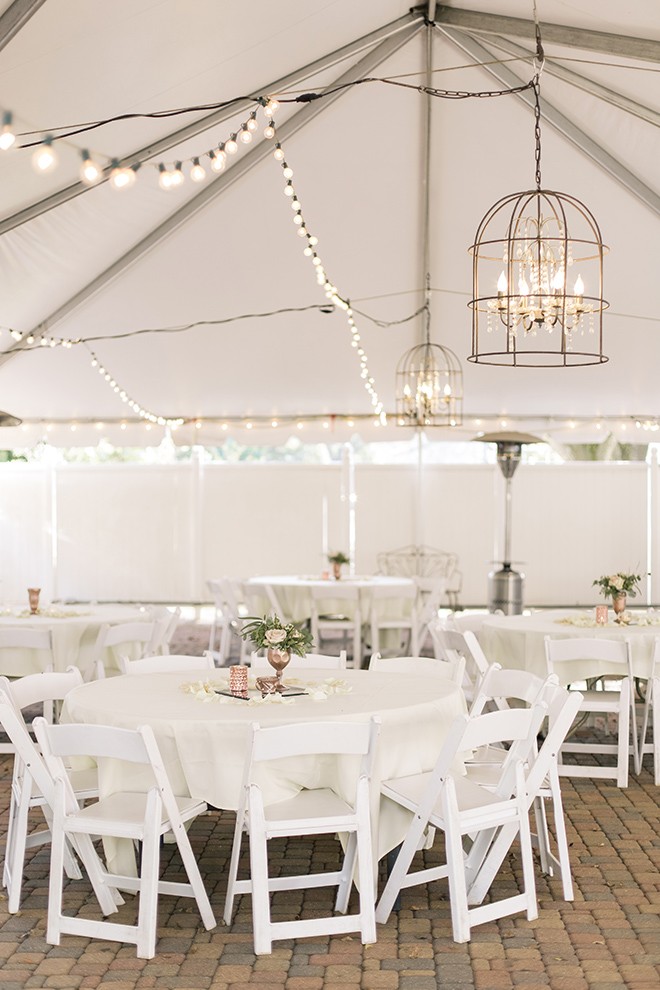 vintage haute flowers wedding, string lights, crystal chandeliers, tented wedding reception, outdoor reception, simple reception table decor, rose gold accents, white reception chairs