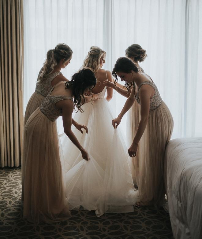 modern elegance wedding houston bridesamaids helping bride get rady