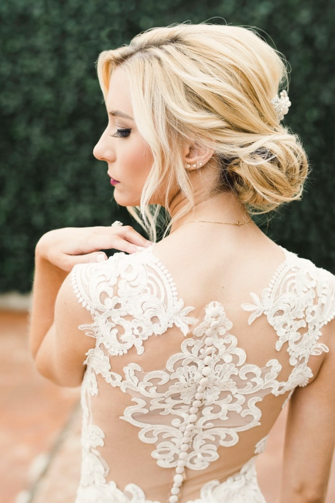 hair and makeup the bridal suite houston low chignon bun loose strands lace dress