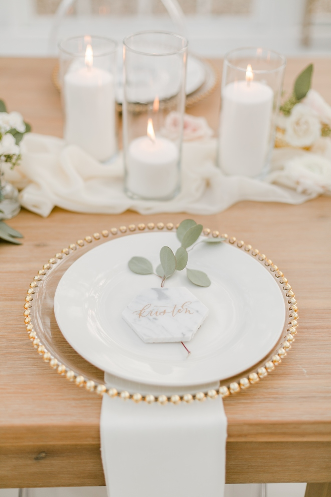 close up flat lay wedding reception place setting gold beaded charger white plate eucalyptus pillar candles amy maddox