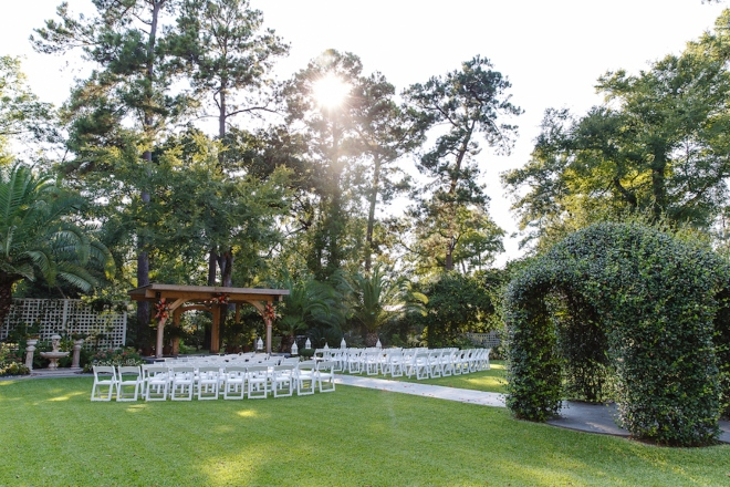 outdoor wedding ceremony lawn white chairs woood arbor trees shirley acres houston venue
