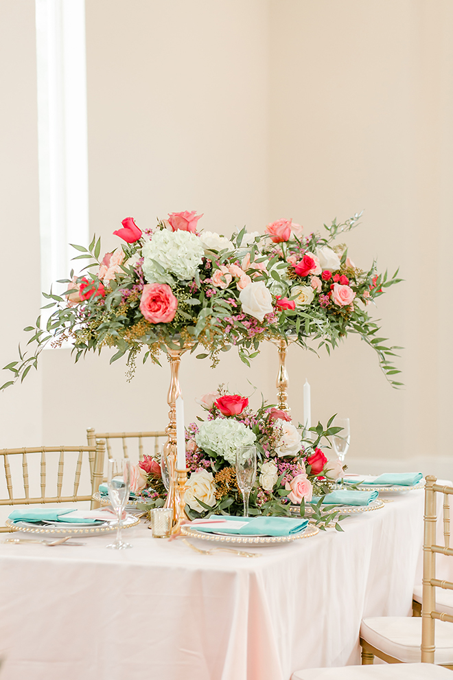 aqua napkins, pop of color, wedding theme, tall centerpieces, gold vase, gold flower stand, gold beaded charger, pink table linens, gold chiavari chairs
