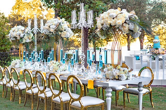 white table, gold clear back chairs, candelabras, tall centerpieces, flowers, wedding tables