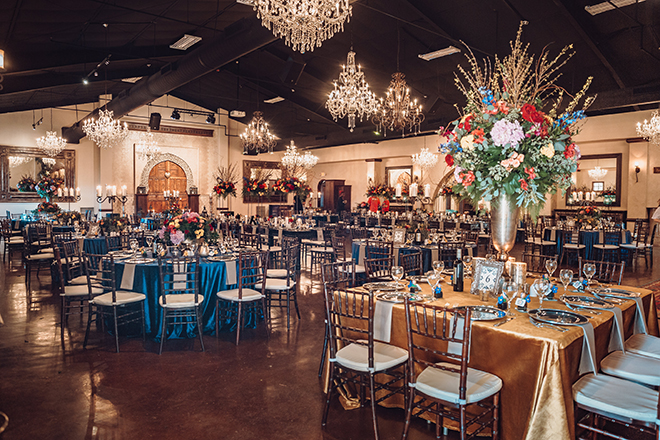 reception decor, madera estates, blue linens, spanish-inspired wedding, chandeliers, candle centerpieces, greenery, table setting, wedding table, gold linens, floral centerpieces
