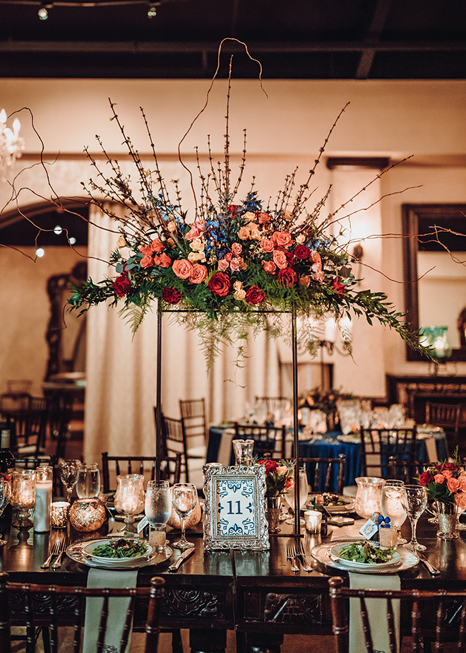 reception decor, madera estates, spanish-inspired wedding, chandeliers, candles, tall floral centerpieces, red, orange, yellow, roses, greenery, table setting, wedding table