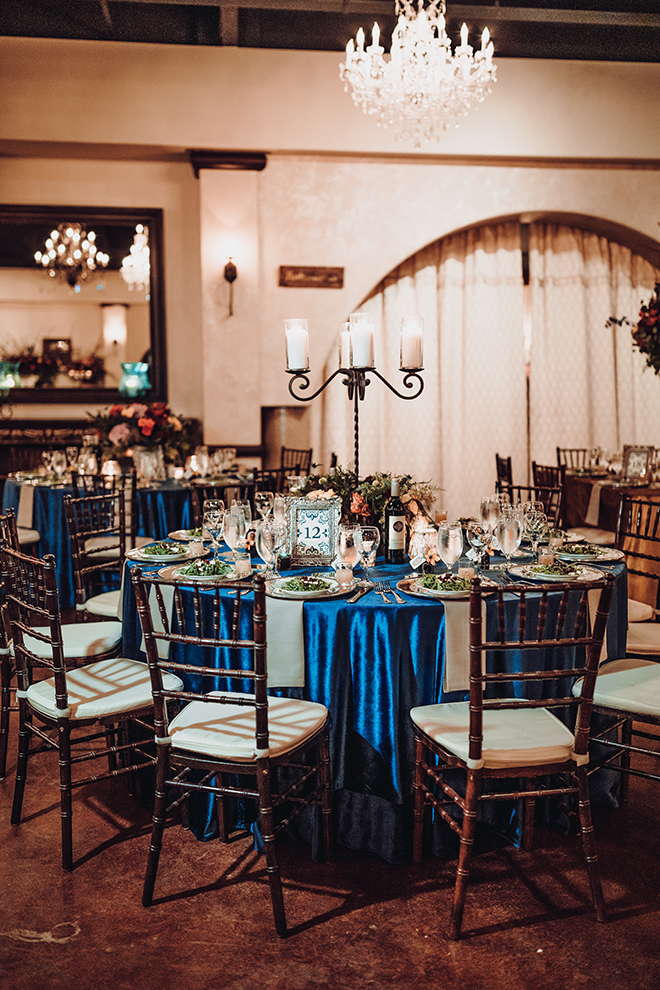 reception decor, madera estates, blue linens, spanish-inspired wedding, chandeliers, candle centerpieces, greenery, table setting, wedding table