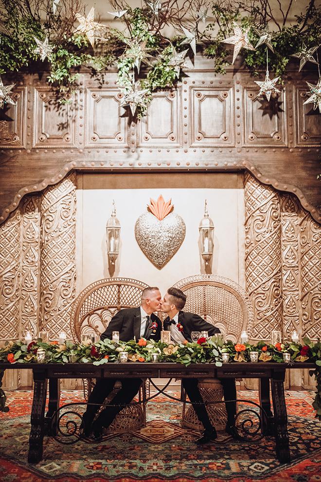 reception decor, couple's table, greenery, red, orange, yellow, flowers, metal, spanish-inspired wedding, same sex wedding, grooms, gay wedding, lgbt