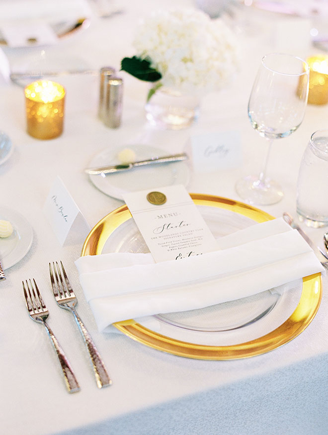 gold chargers, table decor, floral centerpiece, white floral decor, white flowers, candles, classic decorations, plates, wine glasses, elegant