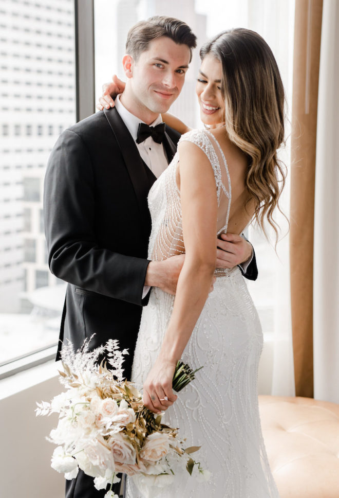 Tuxedo, bride and groom, ring, roses, gold, fern, beaded, open back, wavy hair, bridal style, hotel suite, modern wedding