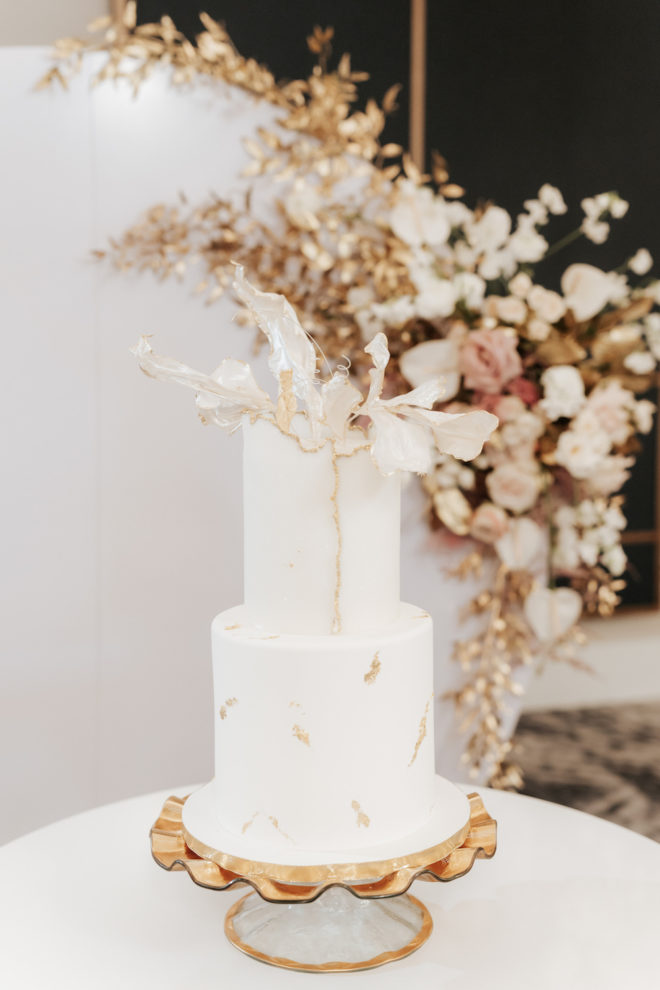 two tier cake, delicate, white, gold, modern, backdrop, floral, roses, cake stand, scalloped, cake table, dessert table, minimalist cake, gilded, ethereal