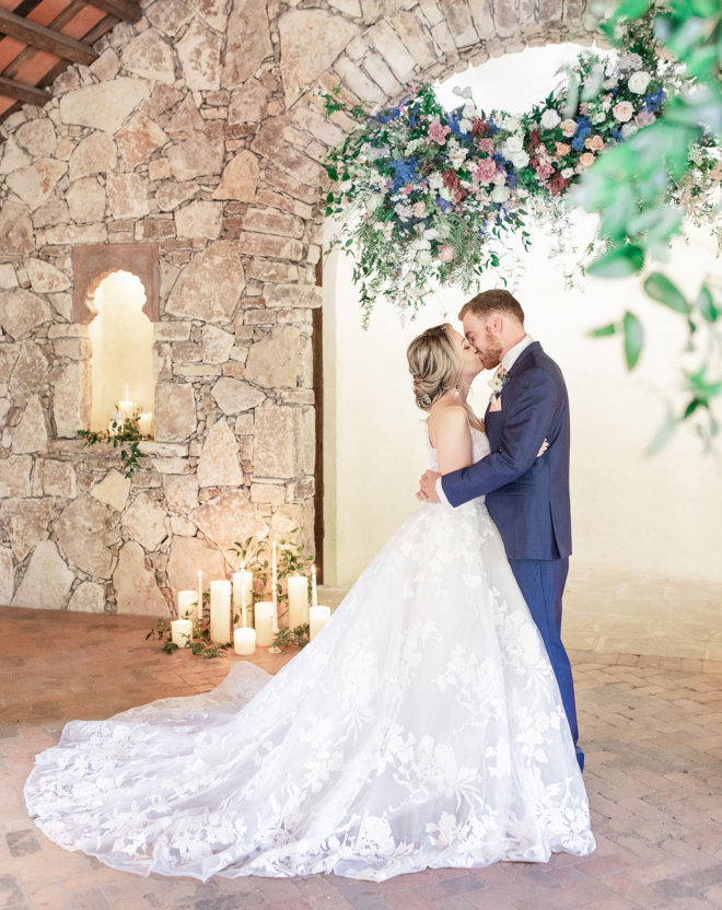 Bride and groom kissing inside Camp Lucys Ian Chapel surrounded by greenery, a pastel colored hanging floral installation and glowing candles