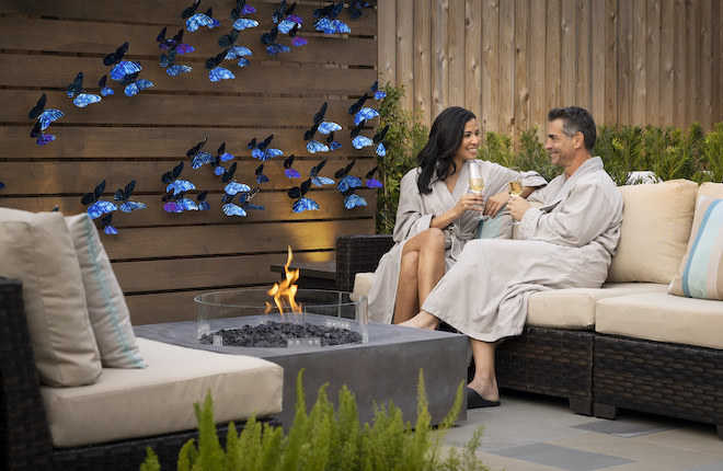 Couple sharing Prosecco by a fire pit a the Trellis Spa