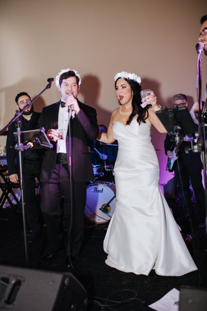 Bride and groom toast in front of band wearing flower crowns.