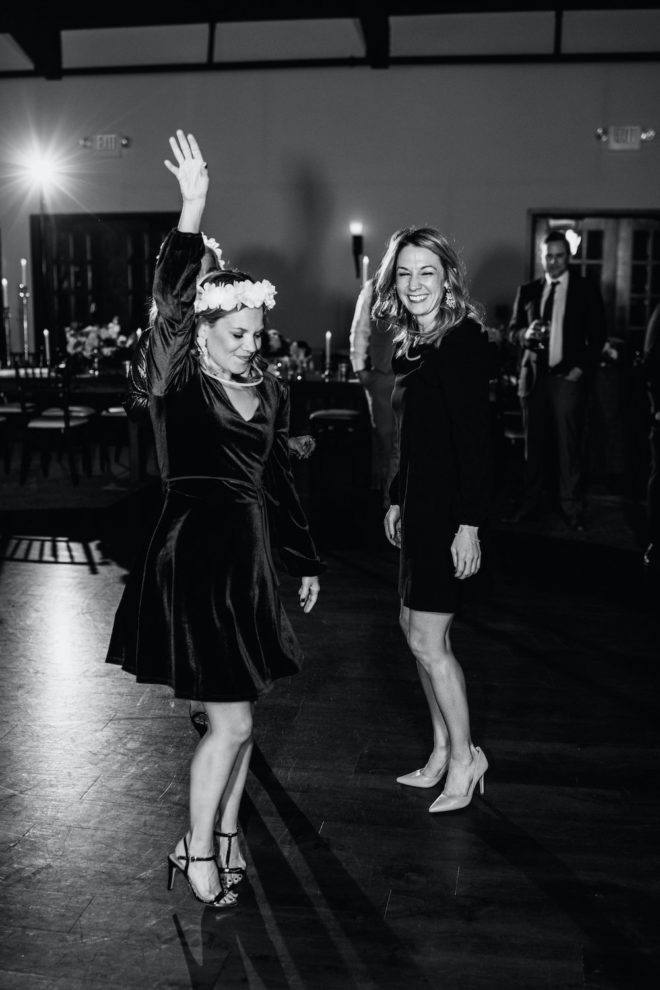 Black and white image of guests dancing at wedding reception.