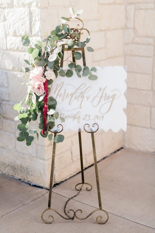 Wedding sign welcoming guests to wedding venue with blush and wine florals.