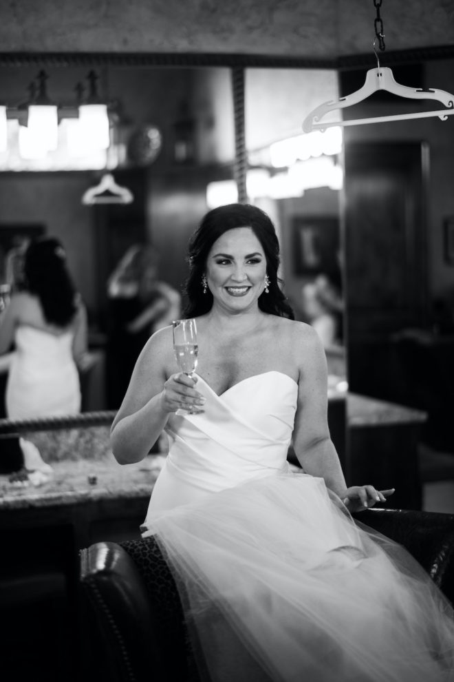 Black and white photo of bride getting dressed in a strapless white gown while drinking champagne.