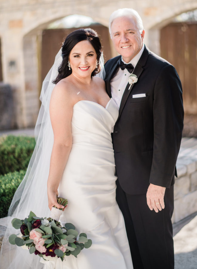 Bride with bouquet of blush and wine colored flowers standing with her father in a black suit outside by green bushes and white austin stone facade of briscoe manor wedding venue