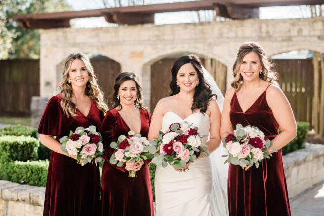 Bride and bridesmaids in wine dressed with wine and blush bouquets.