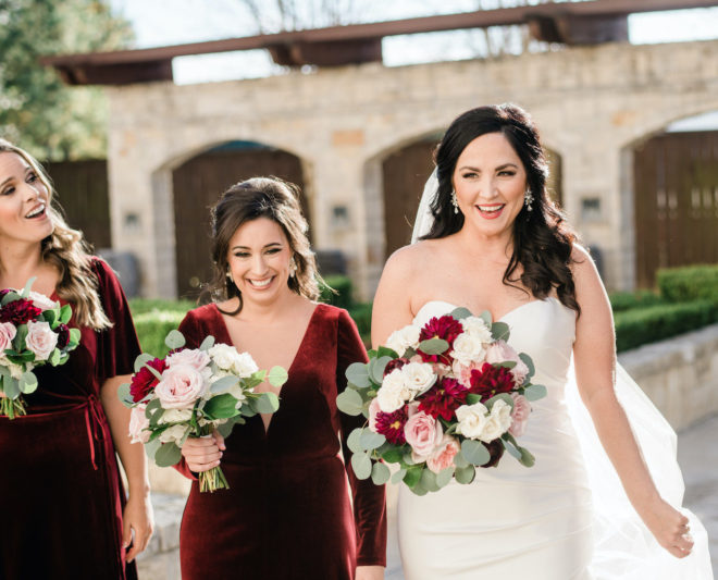 Bridesmaids wearing wine colored velvet dresses and holding roses and greenery bouquets laughing outside with bride who is also holding wine and blush colored rose bouquet outside of Briscoe Manor wedding venue