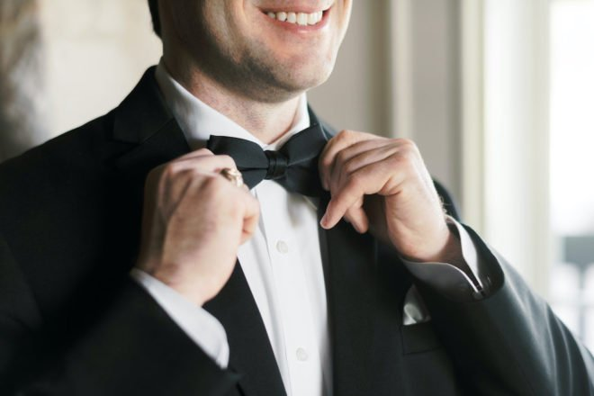 Man adjusts bowtie to get ready for wedding.