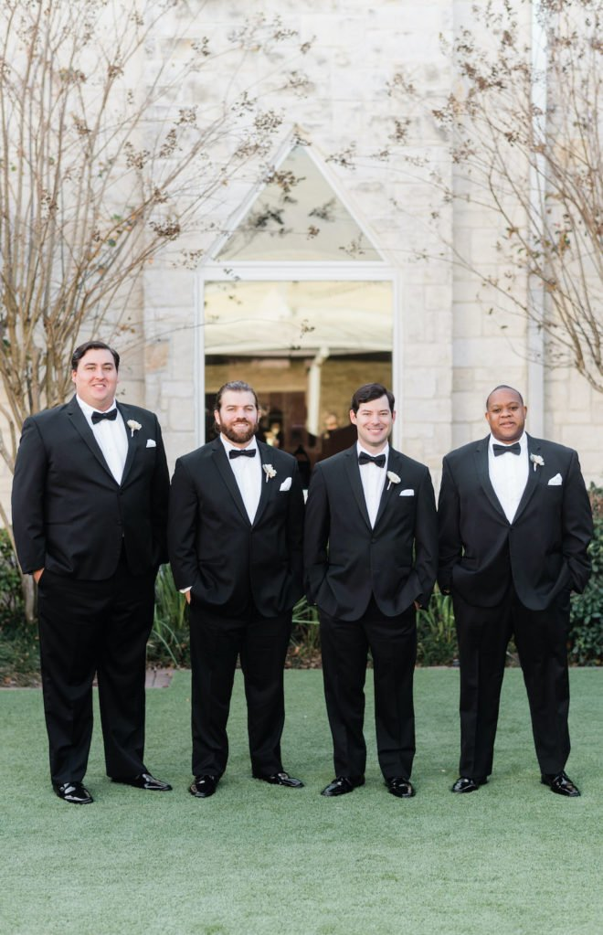 Groomsmen in black tuxes with blush and wine florals.