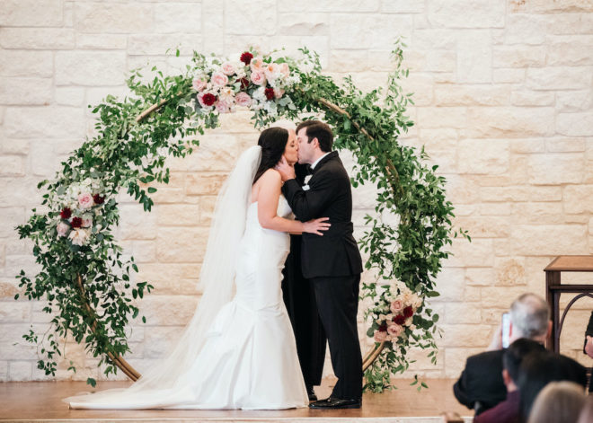 Couple kissing in front of arched alter of blush and wine florals.