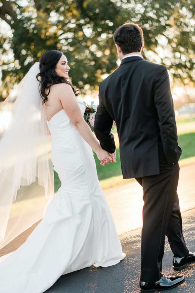 Bride in strapless white dress with veil walking with husband in black tux.