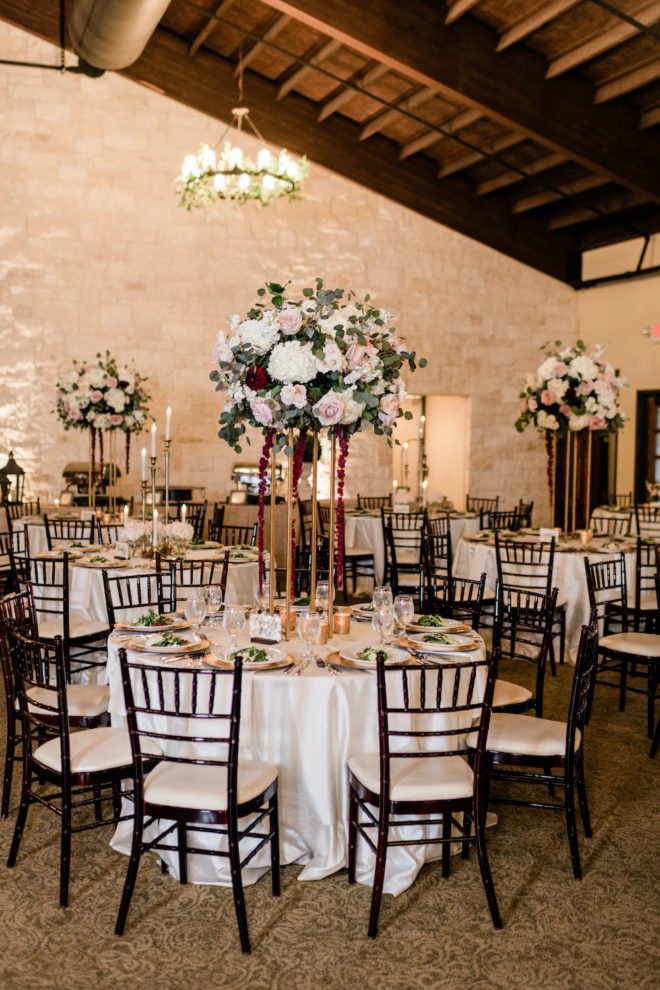 Blush and wine floral reception table arrangement.