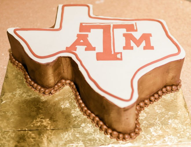 Grooms cake shaped like the state of Texas with burnt orange lettering with the abbreviation for Texas ATM University
