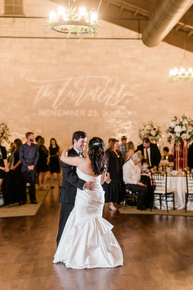Couple dancing at reception in front of personalized name light wall.