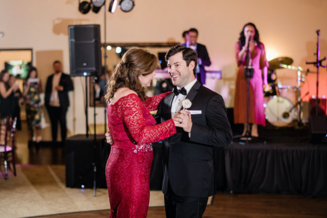 Mother and son dance at wedding in front of a live band.