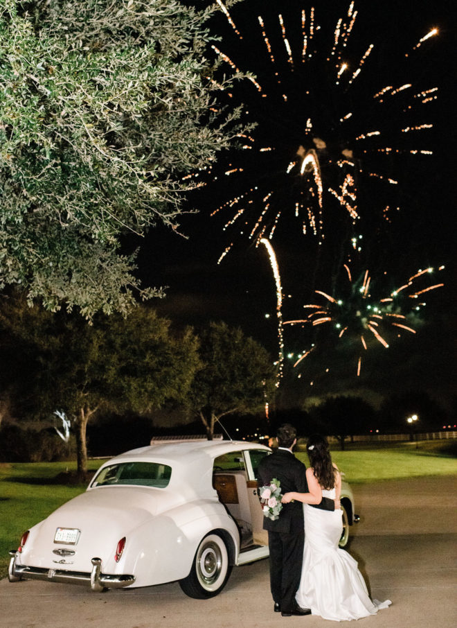 Bride and groom standing by Rolls Royce car and watching fireworks in distant at Briscoe Manor