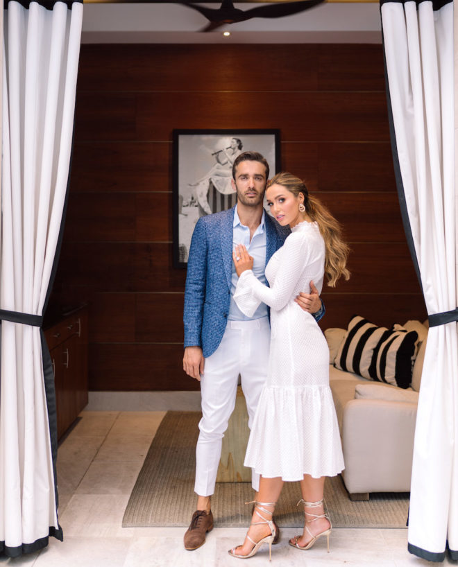 Man in blue suit jacket and white slacks and loafers posing with woman in mid length white dress and stiletto heels inside of luxury pool side cabana at Post Oak Hotel