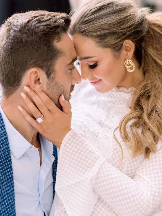 Bride, wearing white textured dress and gold earrings, sitting on grooms lap with her forehead against his