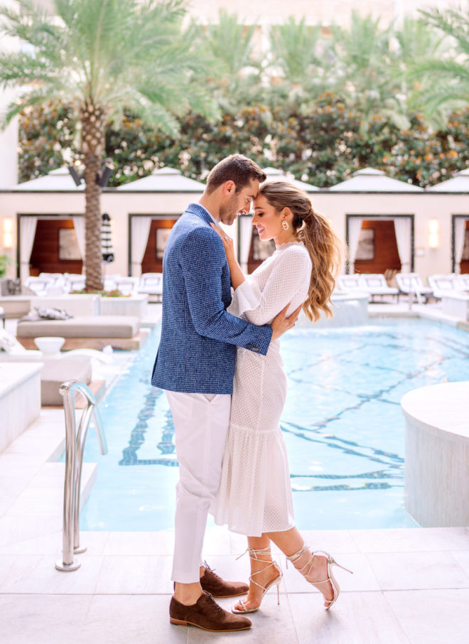 Man in blue blazer and brown loafers holding woman with ponytail, stiletto heels and ankle length dress in front of the Post Oak Hotel's pool and cabanas