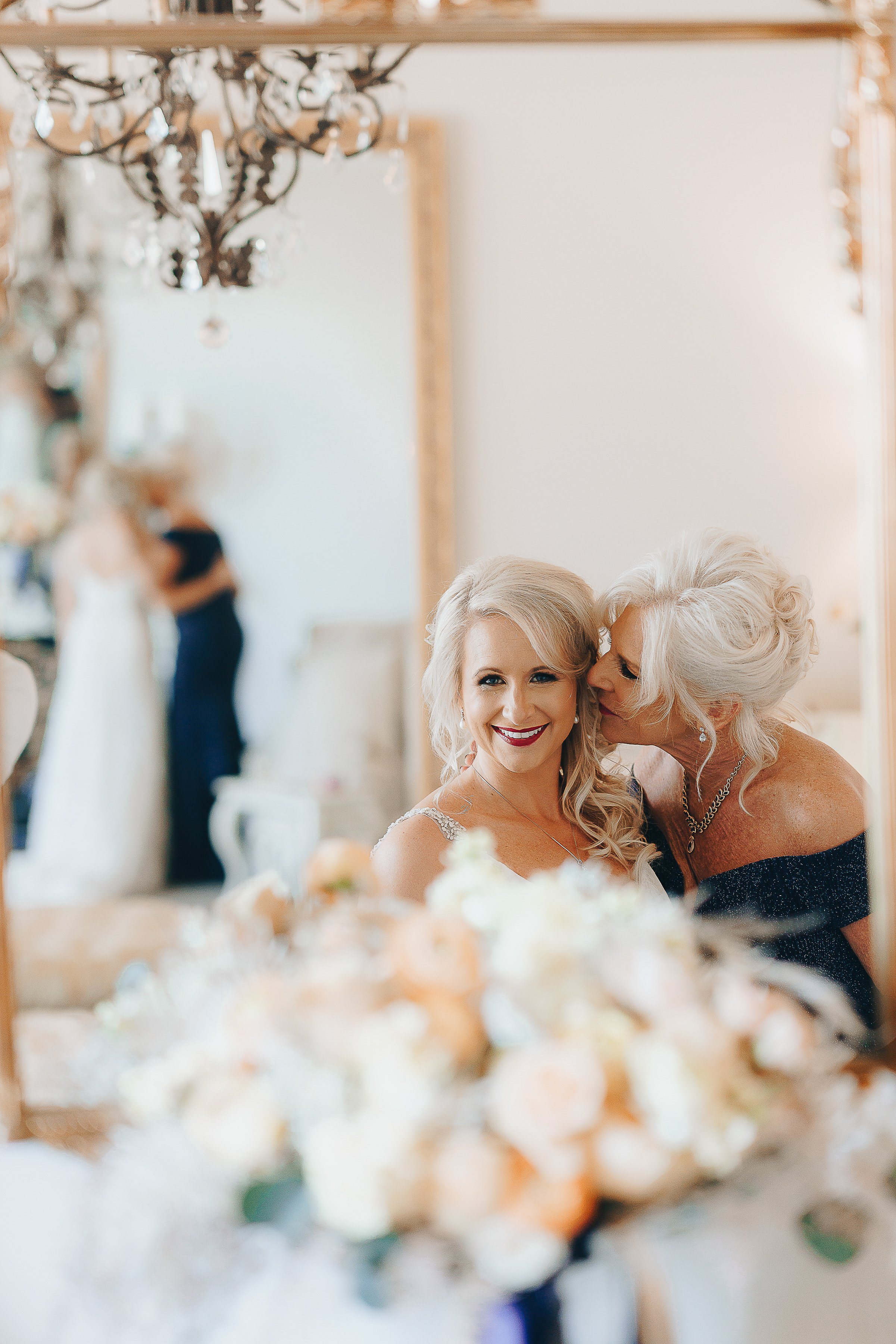 Mother of the Bride kissing the bride on the cheek.