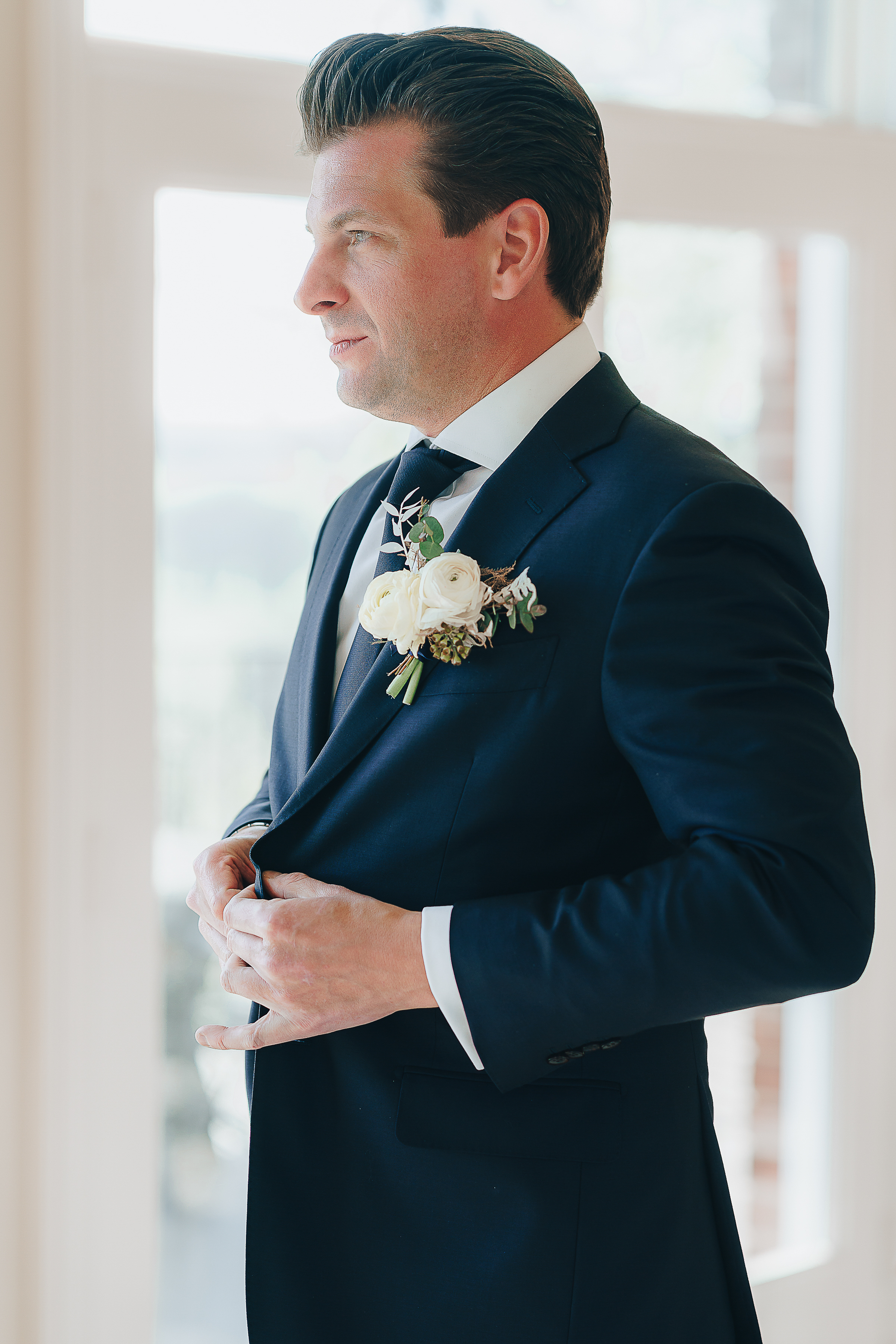 Groom buttoning his suit jacket.