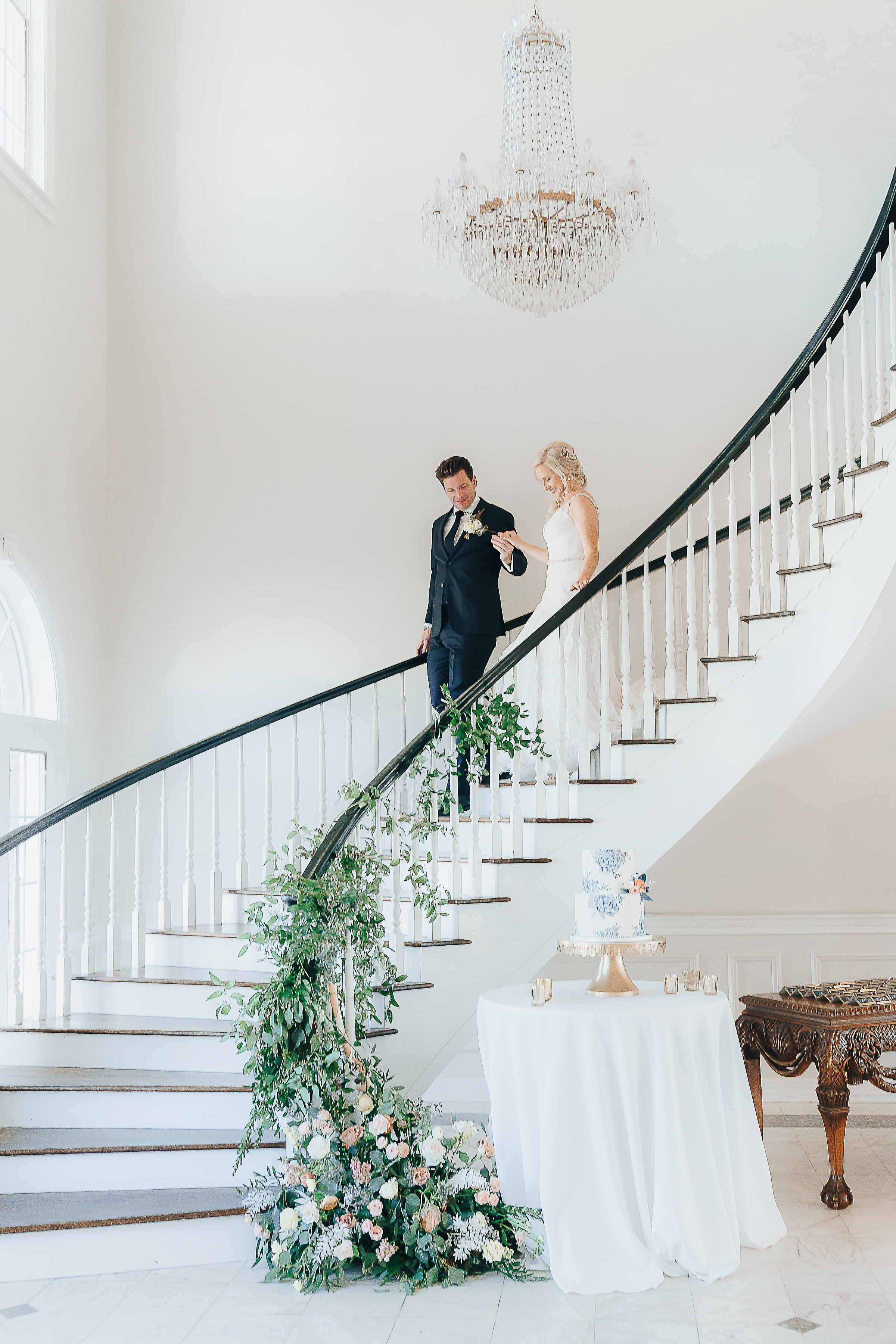Groom walking the Bride down a curving staircase with their cake display at the bottom