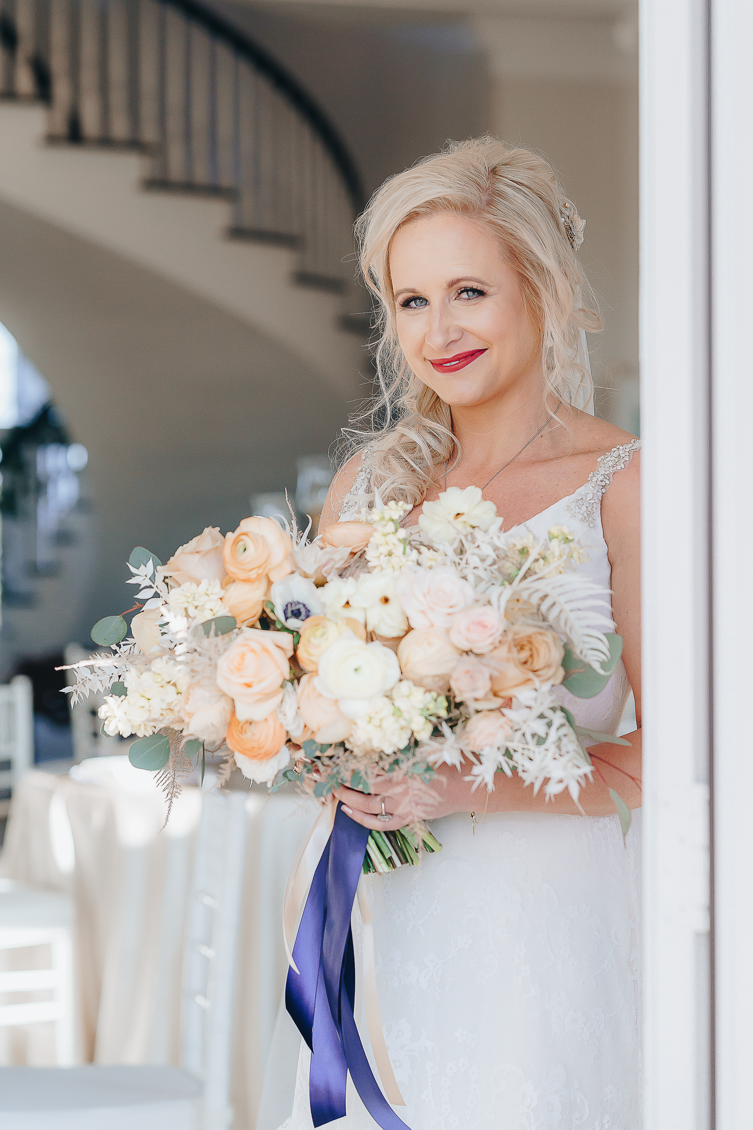 Bride holding a bouquet of blush, peach and white flowers tied by a navy ribbon.