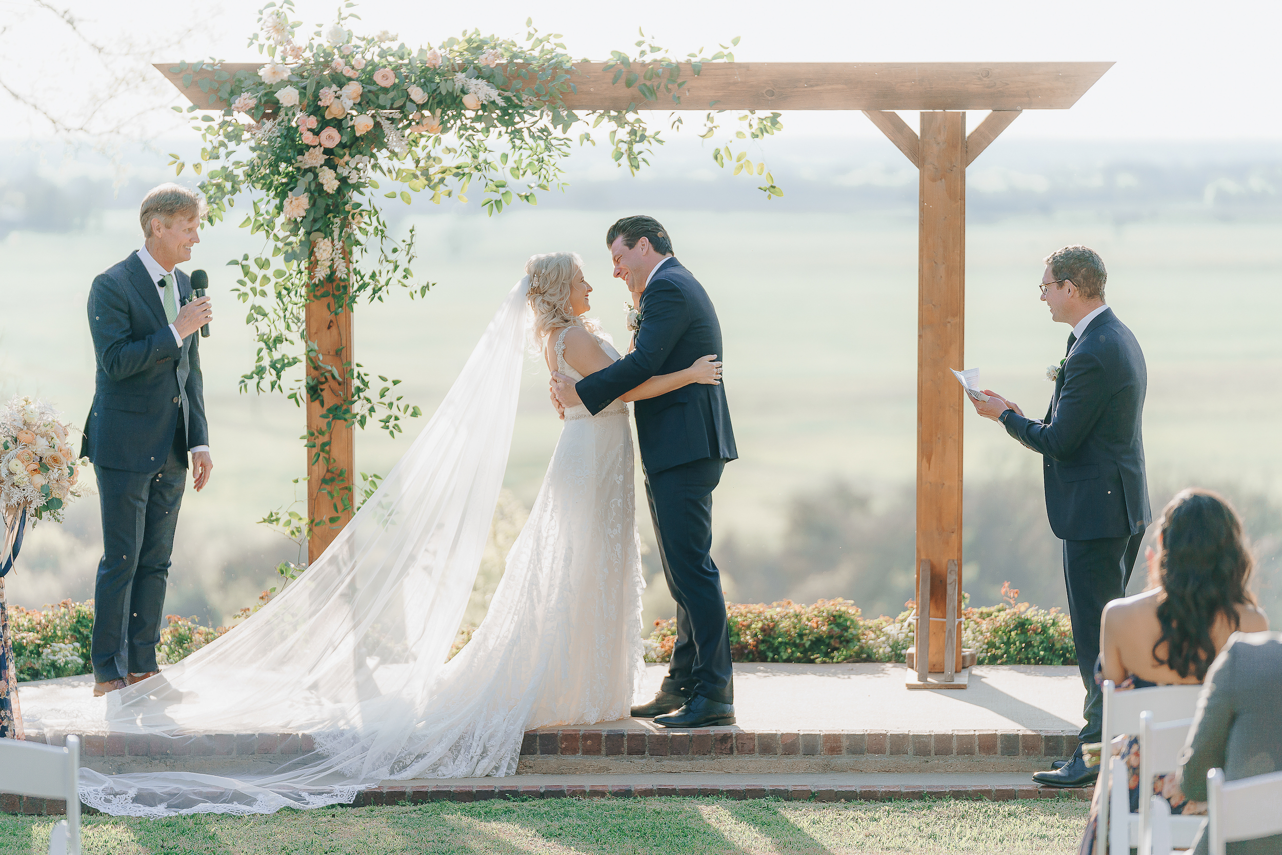 Bride and groom embracing at the altar with a view of the Hill Country.