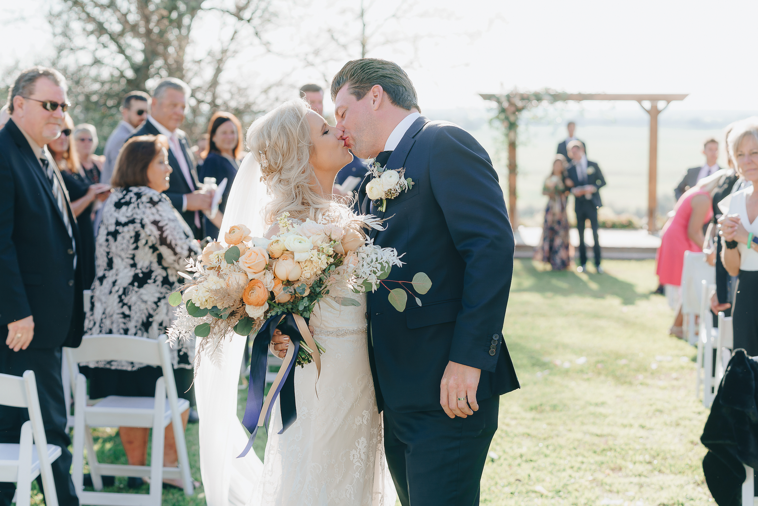 Bride and Groom kissing at the end of the aisle.