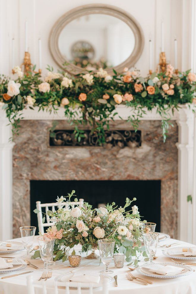 Fireplace adorned with peach and blush florals and greenery behind table set with lush blush botanicals, white linens and blush accents inside of the Mansion at ColoVista