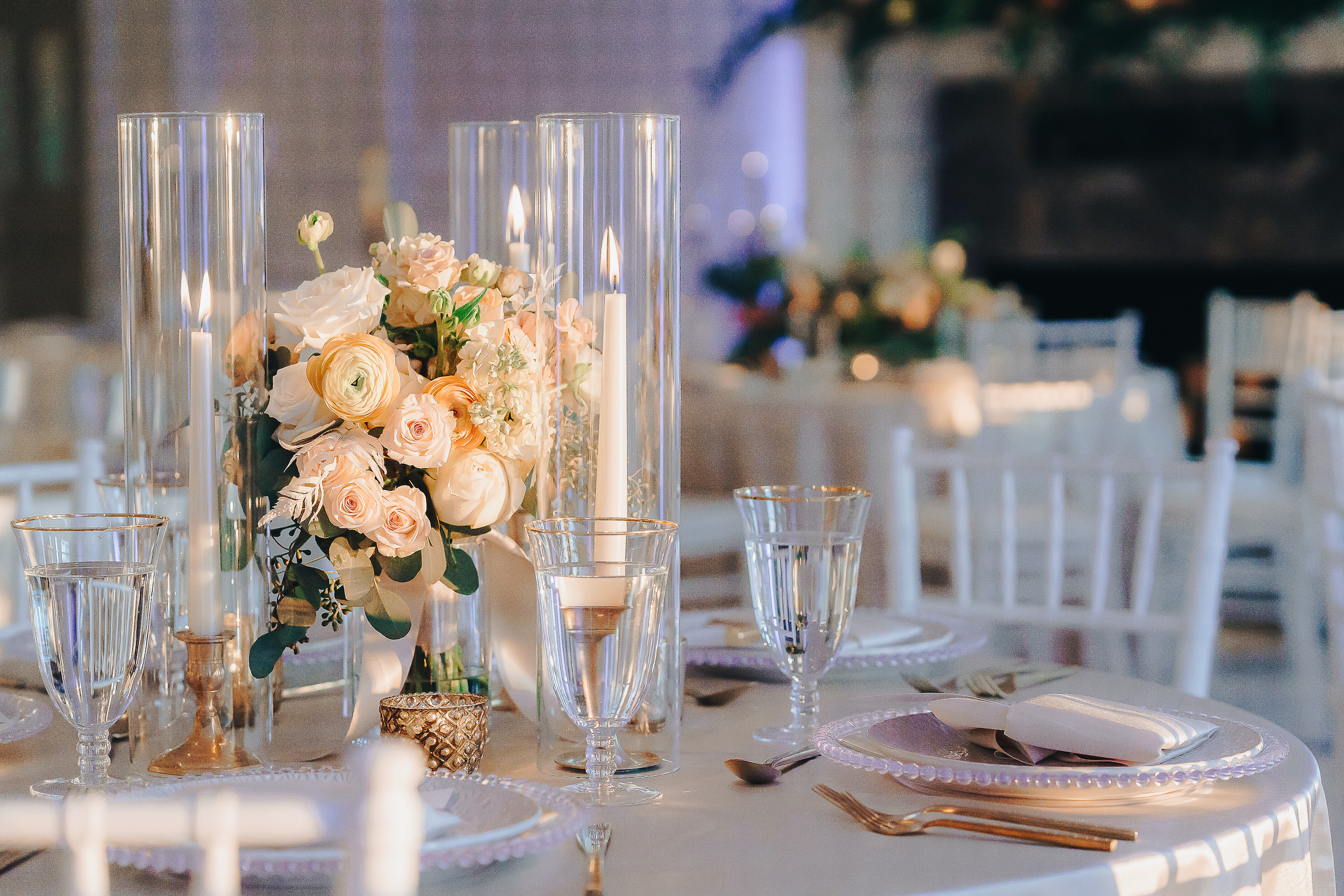reception table decor, white and peach flowers and glass candle covers