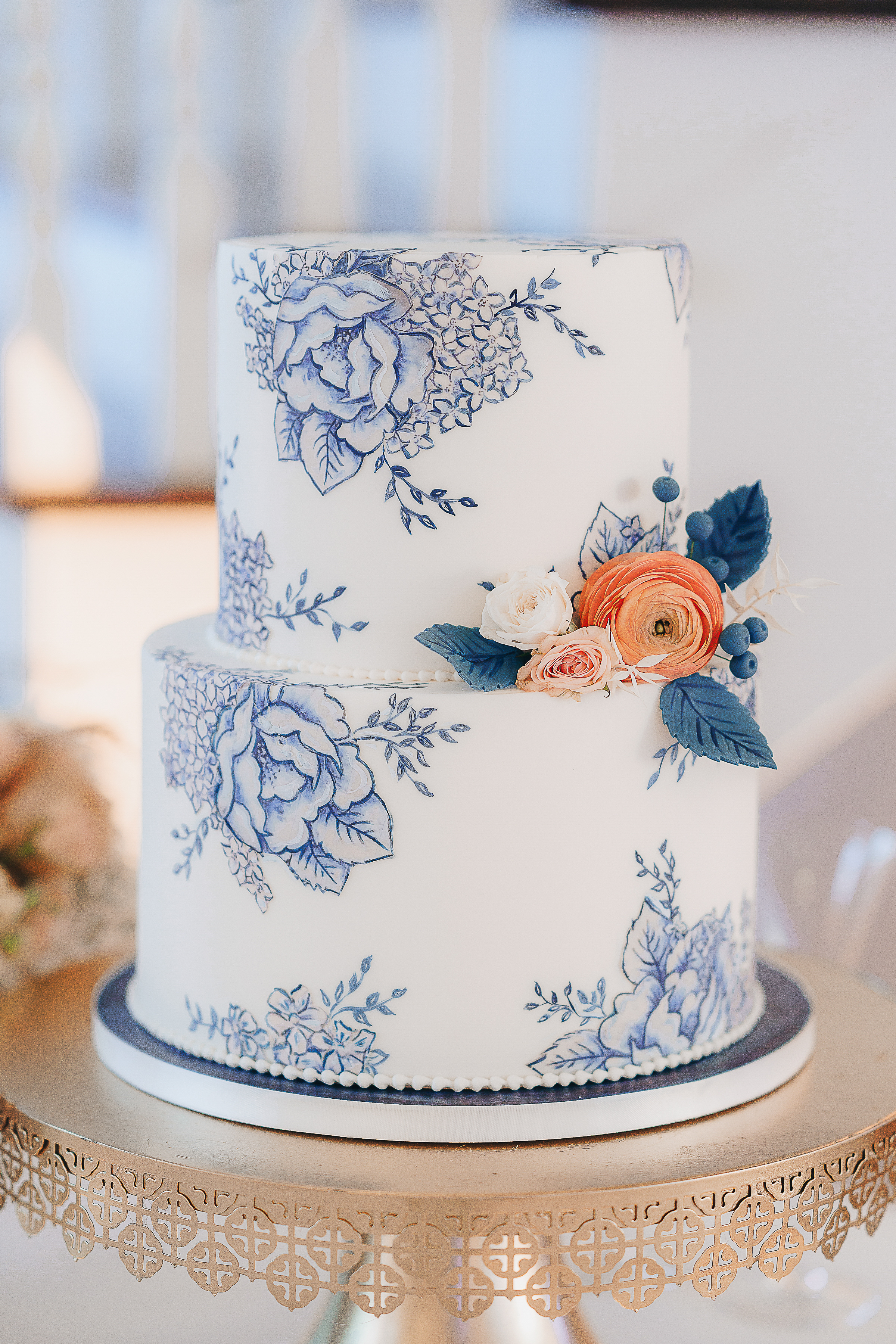 Charming hill country two-tier wedding cake with painted navy flowers atop a gold cake stand.